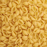 Pile of conchiglie yellow pasta as abstract background Royalty Free Stock Photos