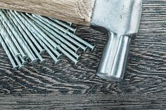 Pile of construction nails claw hammer on wooden board.  Royalty Free Stock Photography
