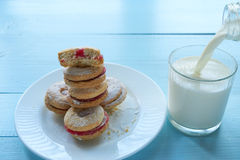 Pile of cookies on white plate and pouring milk Stock Photos
