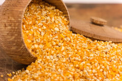 Pile of Corn Grits. A pile of corn grits  in a wooden vessel on a wooden background Royalty Free Stock Photos