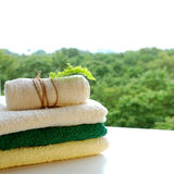 Pile of cotton towels, napkins on a white board against the green summer forest landscape and horizon. Spa, relax and natural Royalty Free Stock Images