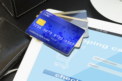 Pile of credit cards with virtual shop on screen Stock Photos