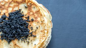 Pile of crepes with black caviar Royalty Free Stock Image