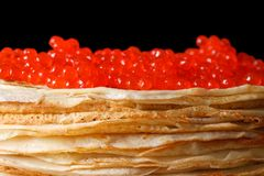 Pile of crepes with red caviar macro isolated on black Royalty Free Stock Photography
