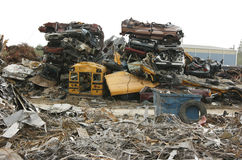 Pile of Crushed Cars at Scrap Yard. A large pile of crushed automobiles including a school bus, a van and a pickup truck waiting to be recycled stock image