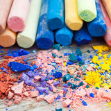 Pile of crushed chalk closeup and rainbow colored pastel crayons Royalty Free Stock Images