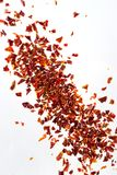 Pile crushed dried red pepper flakes, on white background, top view royalty free stock image