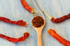 Pile crushed red pepper, flakes and seeds on the wooden table royalty free stock images