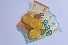 Pile of crypto currency coins over Euros royalty free stock photography