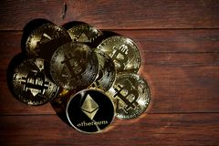 Pile of cryptocurrencies placed on wooden table. Ethereum as most important cryptocurrency concept. Pile of cryptocurrencies placed on the wooden table royalty free stock image