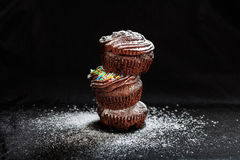 A pile of cup cakes on a black background. A pile of cakes on a black background Stock Photo