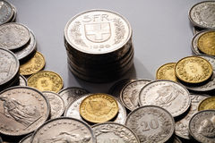 Spot light on Swiss Francs. A pile of current, legal tender Swiss Francs (CHF), with a stack of 5 Franc coins spot lit in the center Stock Image