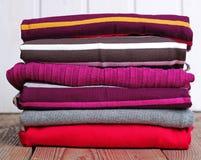 Pile d'habillement de tricotage chaud sur une table en bois Images stock