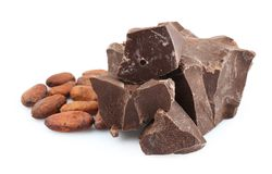 Pile of dark chocolate chunks and cocoa beans. On white background Stock Image