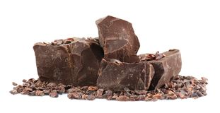 Pile of dark chocolate chunks and cocoa nibs. On white background Royalty Free Stock Photo