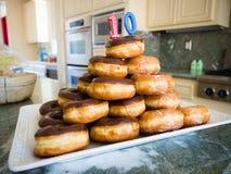 Pile de beignets avec la bougie de 10 ans Photos libres de droits
