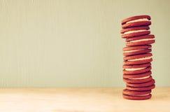 Pile de biscuits au-dessus de table en bois à côté de tasse de café l'image est rétro style filtré Photo libre de droits