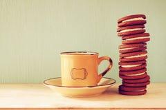 Pile de biscuits au-dessus de table en bois à côté de tasse de café l'image est rétro style filtré Photo stock