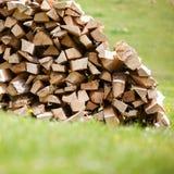 Pile de bois de chauffage coupé avec l'herbe verte Photographie stock