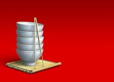 Pile de bols de riz sur un couvre-tapis en bambou Images stock