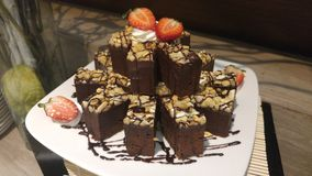 Pile de 'brownie' avec la fraise dans le plat de whith Photo libre de droits