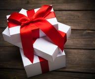 Pile de cadeaux de Noël blancs sur le fond en bois foncé Image stock