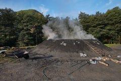 Pile de charbon de bois brûlant dans l'extérieur, la Transylvanie Roumanie images stock