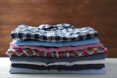 Pile de chemises colorées sur la table Image stock
