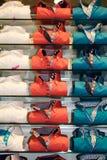 Pile de chemises colorées sur les étagères Photographie stock libre de droits