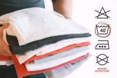 Pile de chemises pliées colorées avec le symbole d'instructions de blanchisserie photo stock