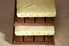 Pile de chocolat noir et blanc sur la table Images libres de droits