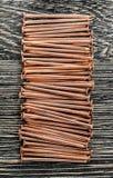 Pile de clous de cuivre sur le conseil en bois photos libres de droits