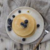 Pile de crêpes avec la myrtille au plat blanc avec la fourchette sur la serviette grise et le fond en bois blanc images stock