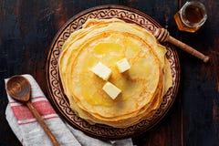 Pile de cr?pes minces faites maison avec des morceaux de beurre, de lait et de miel de vieux plat en c?ramique rustique image libre de droits