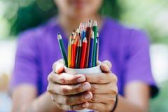 Pile de crayons colorés dans des mains image stock