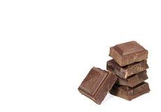 Pile de cubes foncés en chocolat d'isolement sur le fond blanc, avec l'espace libre pour le texte Photographie stock libre de droits
