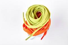 Pile de dentelles de chaussure vertes et oranges Images stock