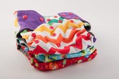 Pile de différentes couches-culottes de tissu de bébé sur le fond blanc Photos libres de droits