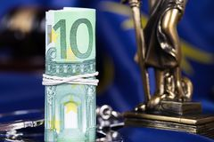 Pile de 100 euros entourés par des menottes sur un drapeau d'UE Photographie stock libre de droits