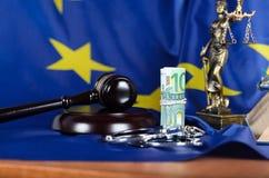 Pile de 100 euros entourés par des menottes sur un drapeau d'UE Photos stock