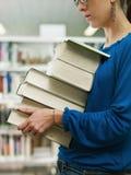 Pile de fixation de femme des livres dans la bibliothèque Photos libres de droits