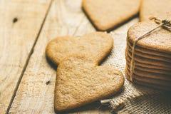 Pile de Ginger Heat Shape Cookies Tied avec la ficelle sur la toile de jute sur le fond en bois superficiel par les agents valent images stock