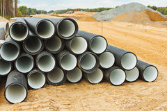 Pile de grands tuyaux sur le chantier de construction Photographie stock