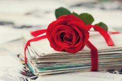 Pile de la carte postale et de la photographie attachées avec le ruban de velours et la rose de rouge Photographie stock libre de droits