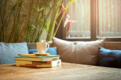Pile de livre avec la tasse de café sur le dessus sur la table en bois Photographie stock libre de droits