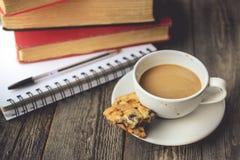 Pile de livre et de biscuits avec du café chaud sur la tasse sale sur le bois B Images stock