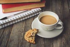 Pile de livre et de biscuits avec du café chaud sur la tasse sale sur le bois B Photo libre de droits