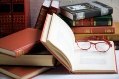 Pile de livres avec les verres rouges placés sur le livre ouvert dans la bibliothèque, le concept d'éducation et de sagesse images libres de droits