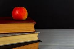 Pile de livres avec une pomme rouge et un tableau noir propre Image libre de droits