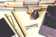 Pile de livres, carnet, ordinateur portable, verres ? l'arri?re-plan de bureau pour l'?ducation apprenant la vue sup?rieure de co photographie stock